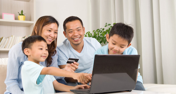 Asian family using laptop to perform online shopping